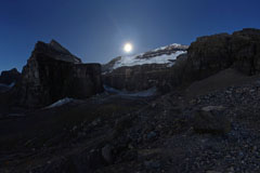 Night photo of moon over victoria mountain, lake louise, plain of six glaciers, alberta